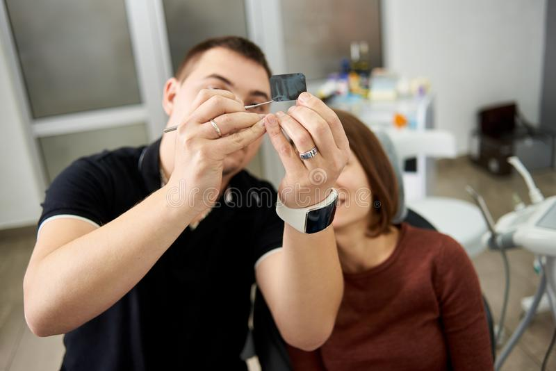 Dentist shows patient features of x-ray teeth shot in clinic stock photo