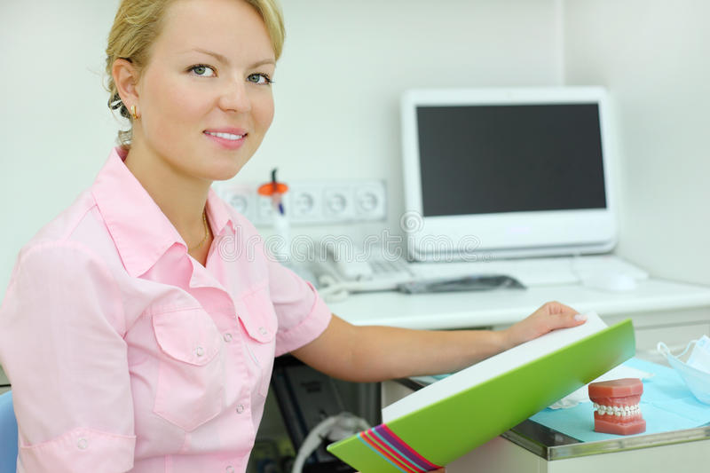Download Dentist Sits At Table In Dental Clinic Stock Photo - Image of notebook, indoors: 26337752