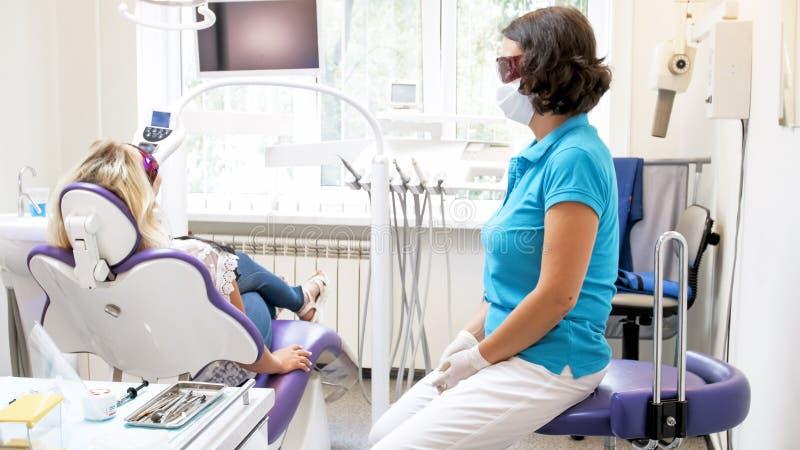 Female dentist sitting next to pateint during teeth whitening procedure. Dentist sitting next to pateint during teeth whitening procedure stock images