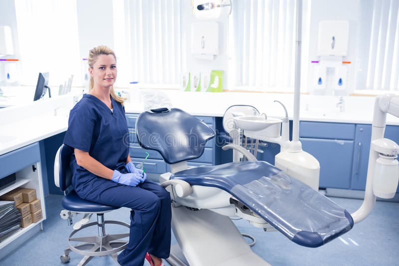 Dentist smiling at camera beside chair stock image