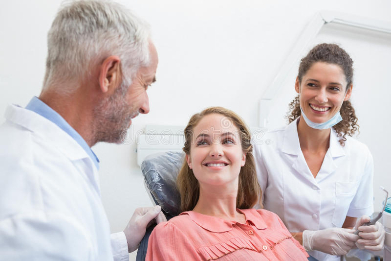 Dentist talking with patient while nurse prepares the tools stock photography