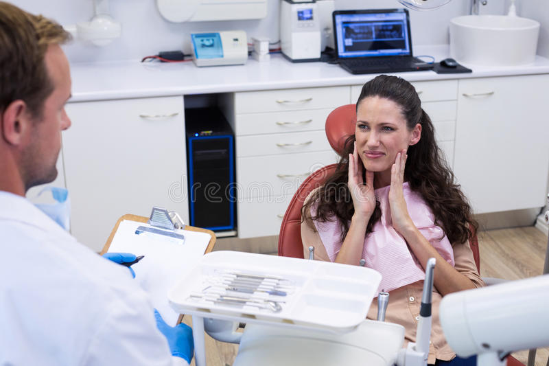 Dentist talking to female patient stock photography