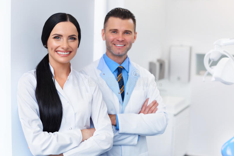 Dentist Team at Dental Clinic. Two Smiling Doctors at their Work. Place royalty free stock image