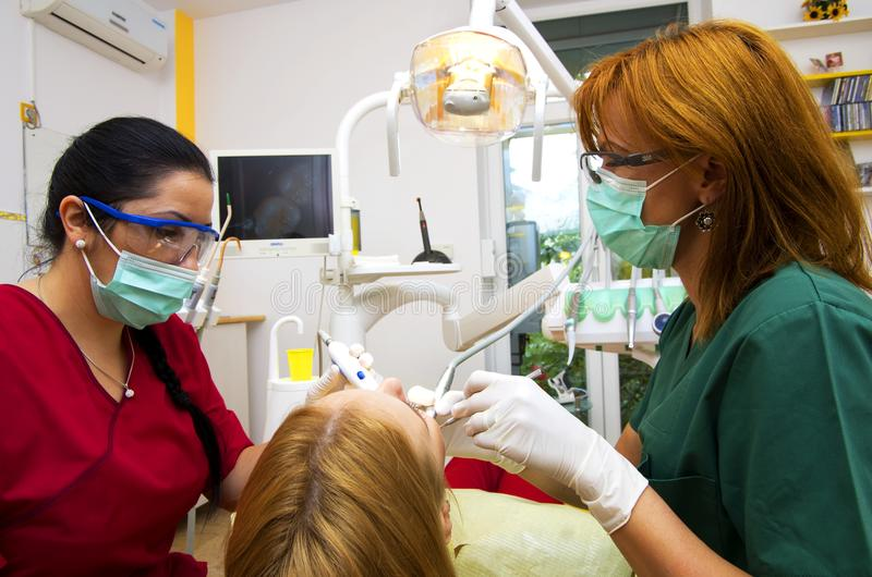 Dentist team working. Dentist and assistant working on a patient using dental tools, teamwork concept royalty free stock photos