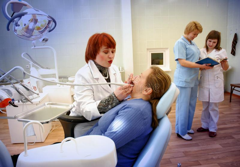 Dentist treats teeth in women royalty free stock photography