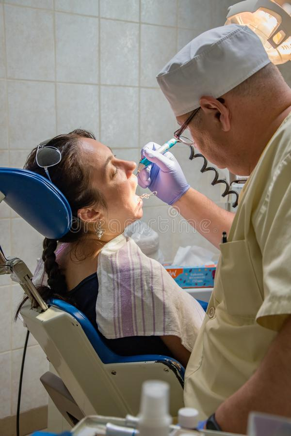 Dentist treats a woman`s teeth, private dental clinic, painless prosthetics at the dentist stock photography