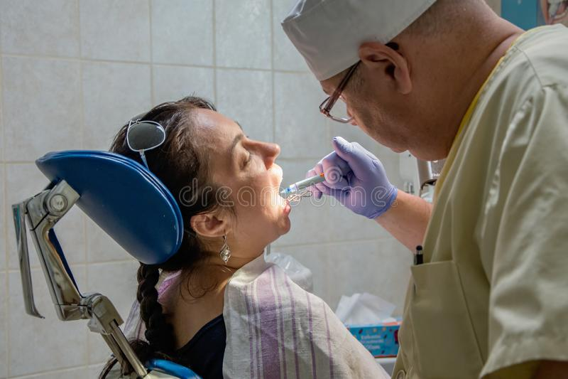 Dentist treats a woman`s teeth, private dental clinic, painless prosthetics at the dentist. 2 stock photos