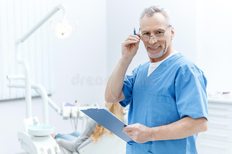 Dentist in uniform with clipboard in dental clinic with patient behind. Senior dentist in uniform with clipboard in dental clinic with patient behind stock photo