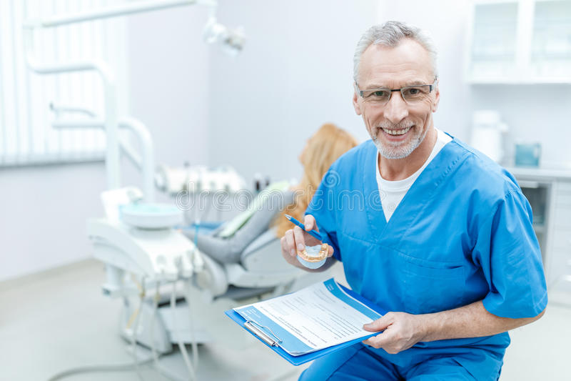 Dentist in uniform with clipboard in dental clinic with patient behind. Senior dentist in uniform with clipboard in dental clinic with patient behind stock photos