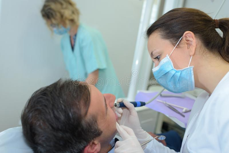 Dentist using implement on patient`s teeth. Dentist royalty free stock photography