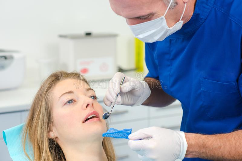Dentist using mirror to see better. Adult stock images