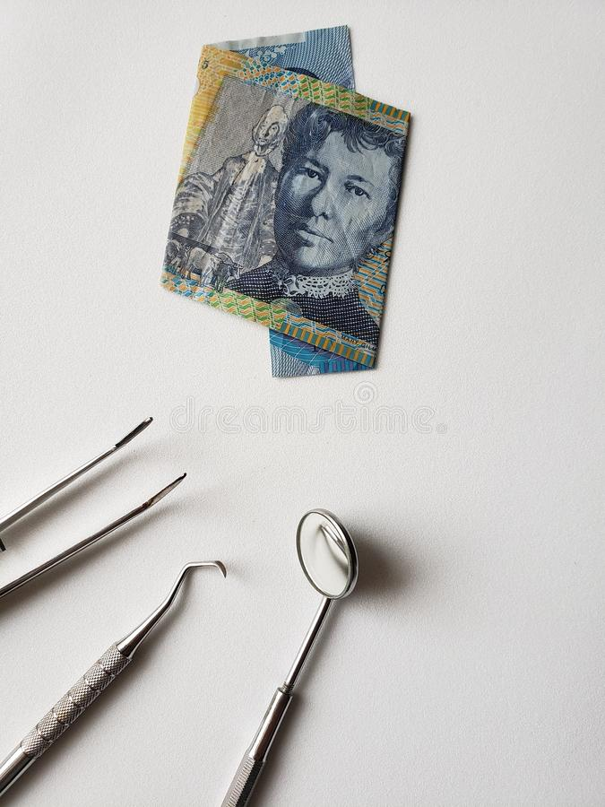 Dentist utensils for oral review and australian banknote of ten dollars. Promotion and offer for oral cleansing, cost of denture care and maintenance, investment stock photo