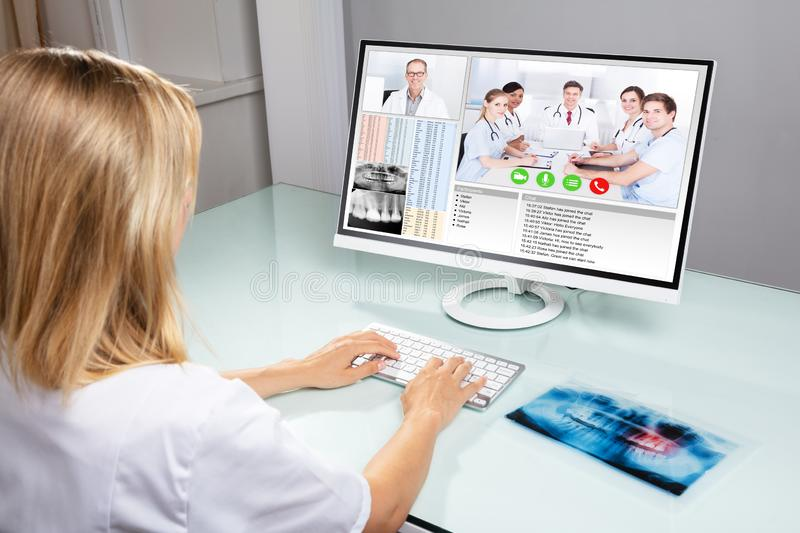 Dentist Video Conferencing With Her Colleagues On Computer. Female Dentist Video Conferencing With Her Colleagues On Computer In Clinic royalty free stock photo