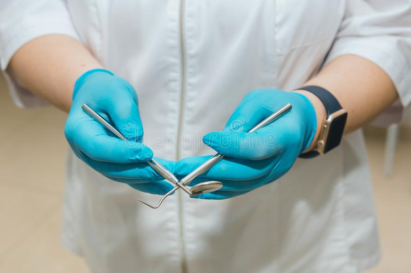 Dentist, in a white coat and blue gloves holds in his hands the tools. royalty free stock image