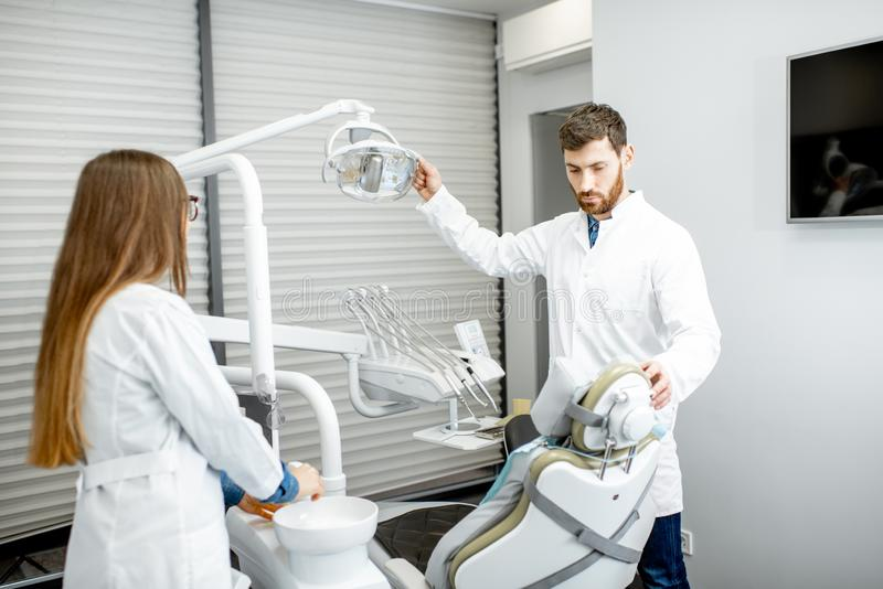 Dentist with woman assistant in the dental office. Dentist with women assistant preparing working place for the procedure in the dental office stock images