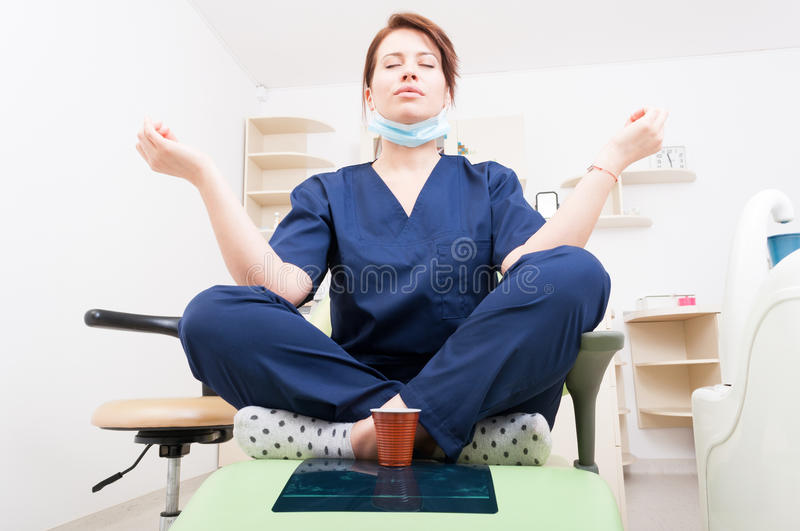 Dentist woman meditating with yoga and lotus position. Coffee break and relaxing lifestyle as a doctor stock image
