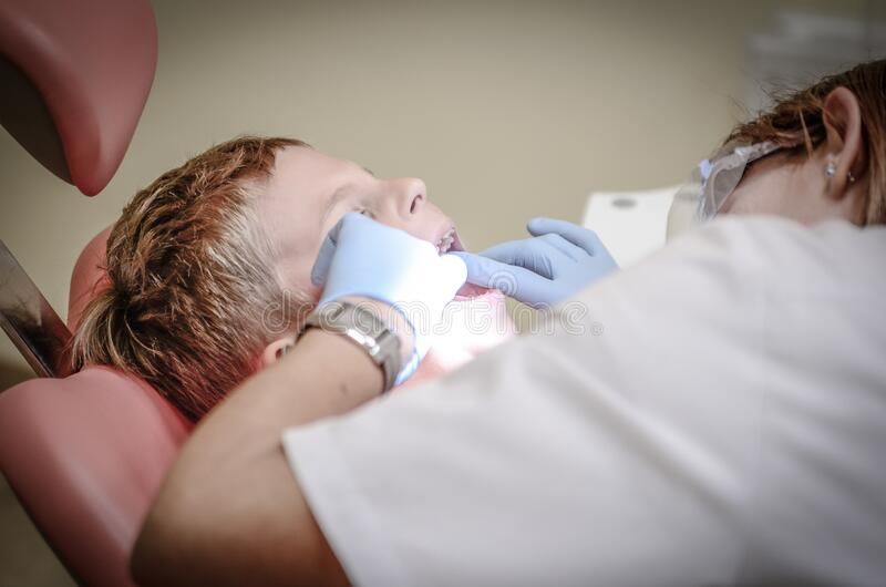 Dentist Woman Wearing White Gloves And White Scrubsuit Checking Boy's Teeth Free Public Domain Cc0 Image