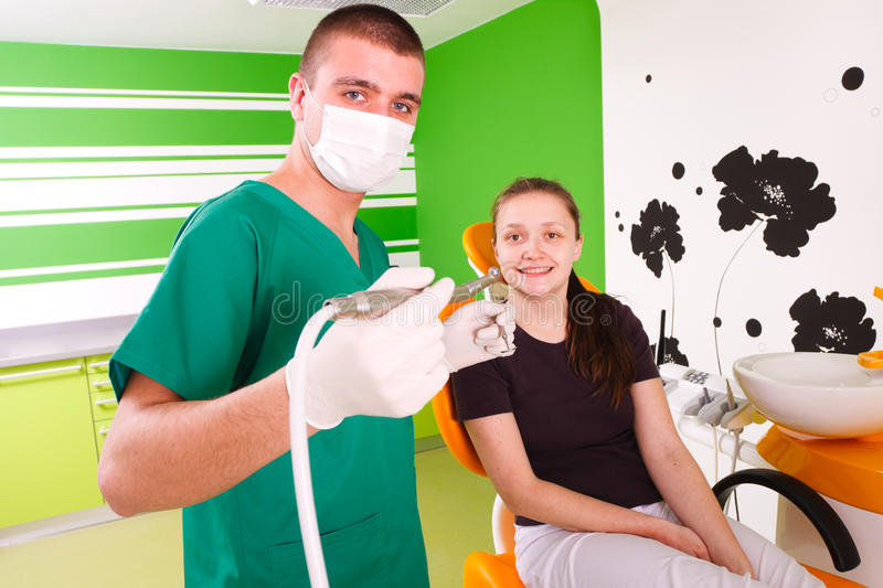 Dentist working. A young male dentist working, treating a young female patient stock photo