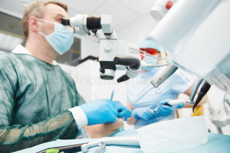 Dentist working at dentistry office with microscope. Dentistry.Dentist male doctor and assistant nurse working with microscope at dentistry office. Focus on tool royalty free stock photography
