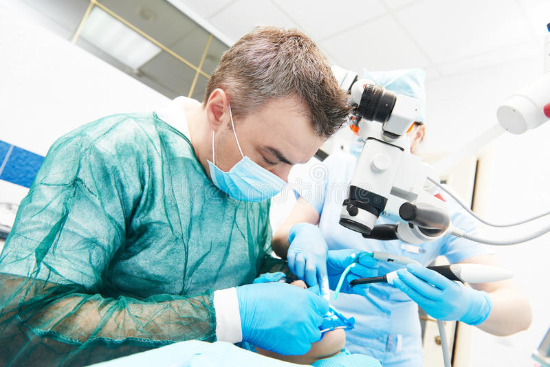Dentist working with microscope at dentistry office. Dentistry. Dentist male doctor and assistant nurse working with microscope at dentistry office royalty free stock photography