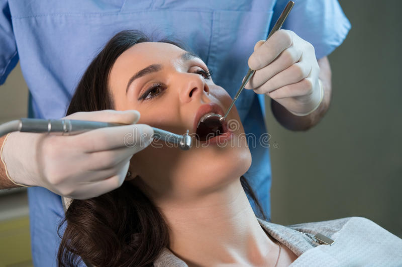 Dentist working on patient. Closeup of dentist examining young woman's teeth royalty free stock image