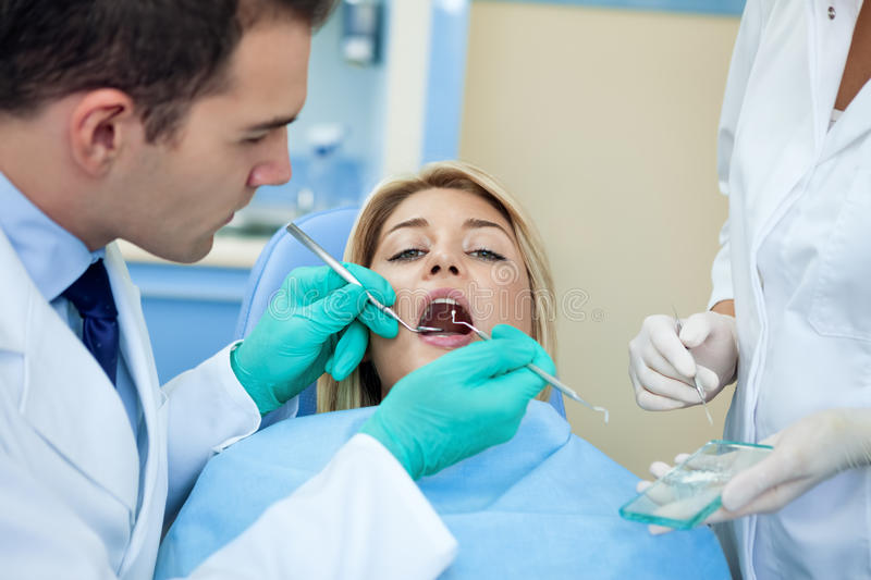 Dentist working. On young female person royalty free stock images