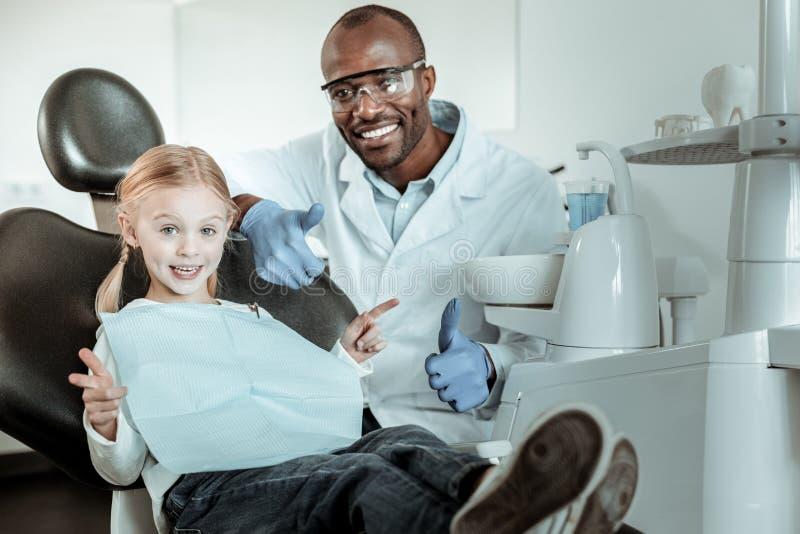 Dentista afro-americano no uniforme completo que senta-se atrás de seu paciente pequeno imagens de stock royalty free