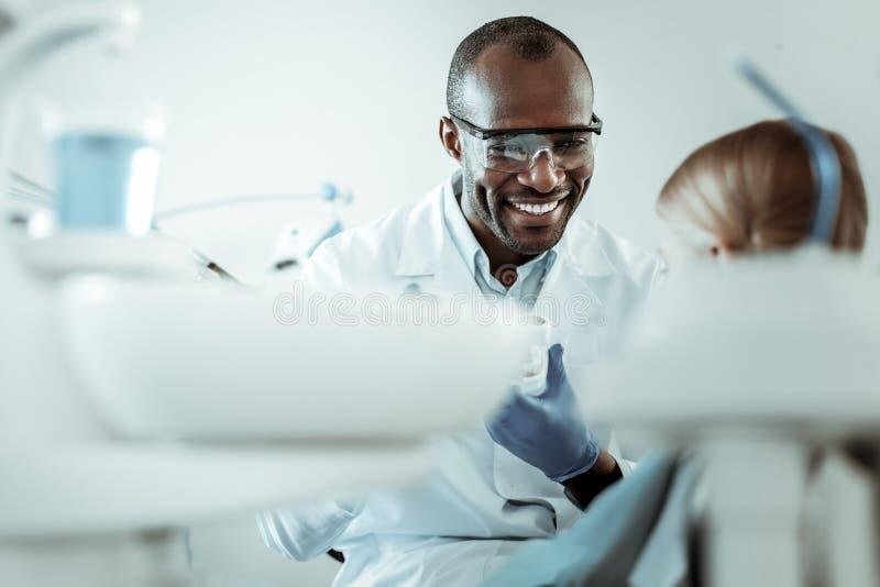 Dentista afroamericano sonriente que trabaja con poco paciente imagenes de archivo