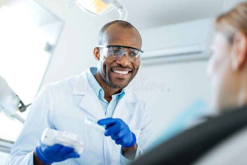 Dentista agradable que explica cómo prevenir la placa dental imágenes de archivo libres de regalías