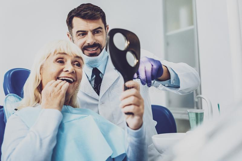 Dentista alegre que se coloca cerca de su visitante imagen de archivo libre de regalías