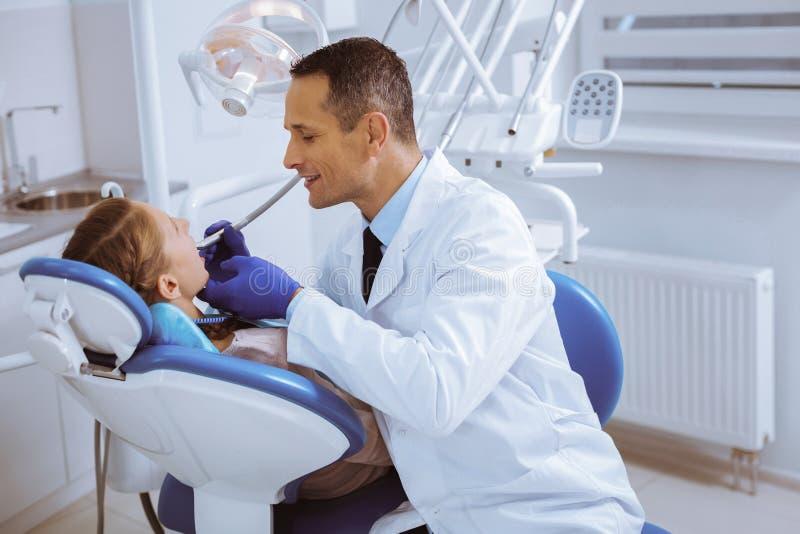 Dentista atento que se sienta cerca de su visitante fotos de archivo