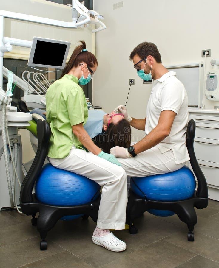 Dentista, ayudante y paciente en clínica dental imagenes de archivo