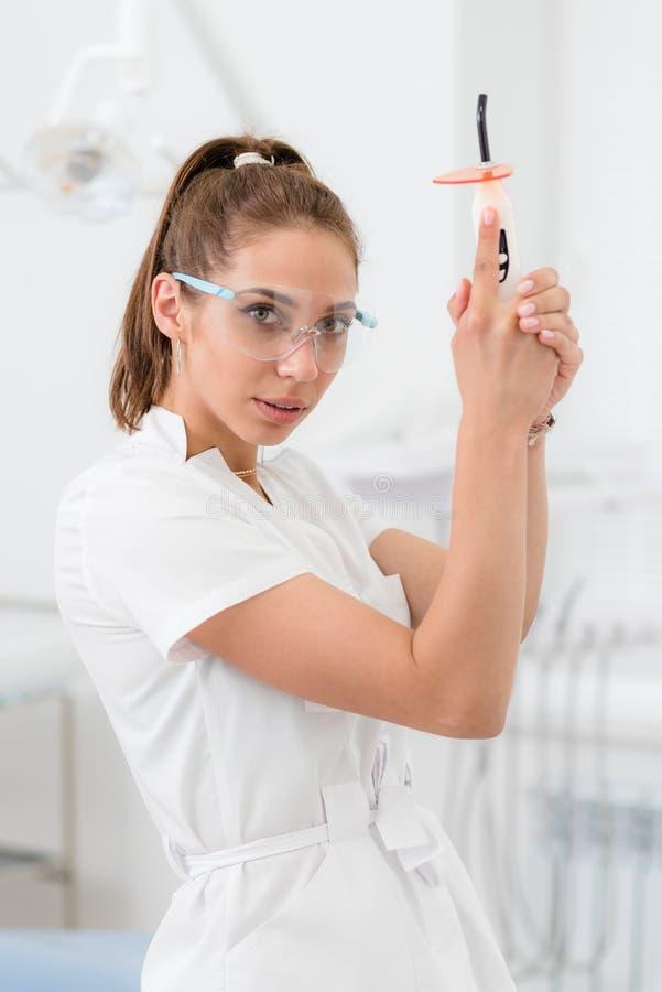 Dentista bonito da menina que levanta com lâmpada da polimerização à disposição no escritório imagem de stock royalty free