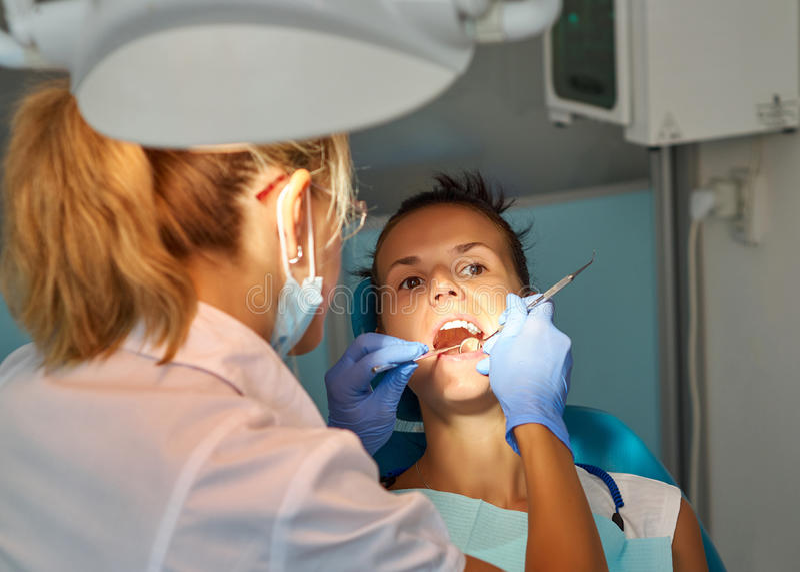 Dentista bonito da mulher que trata um patient& x27; dentes de s no escritório dental imagem de stock royalty free