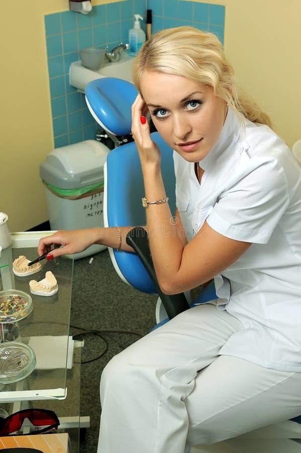 Dentista bonito no escritório médico fotografia de stock