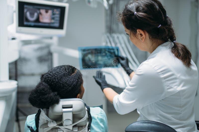 Dentista che considera l'immagine dei raggi x, clinica dentaria immagini stock libere da diritti