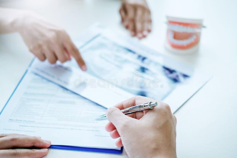 Dentista che consulta il paziente che presenta i risultati su x-r dentario fotografia stock