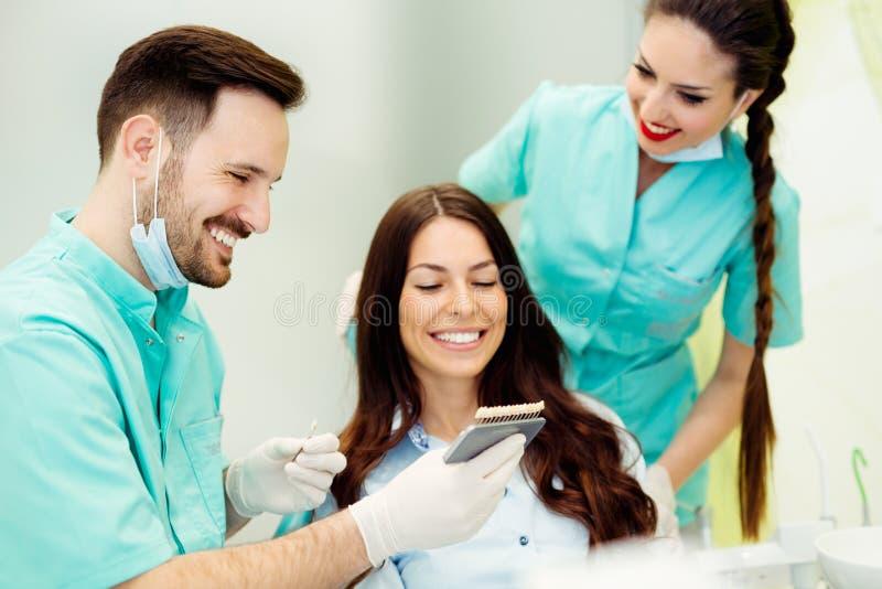 Dentista che controlla e che seleziona colore dei denti del ` s della giovane donna fotografie stock libere da diritti