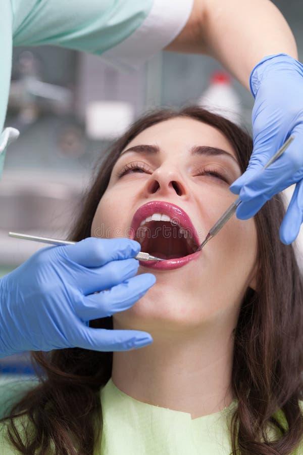 Dentista che cura un paziente femminile fotografie stock libere da diritti