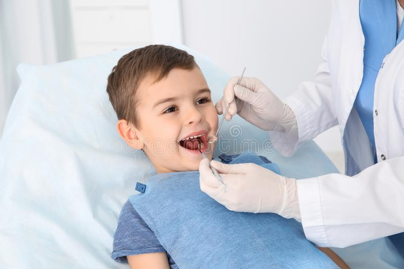 Dentista che esamina i denti del ragazzo sveglio in clinica fotografia stock