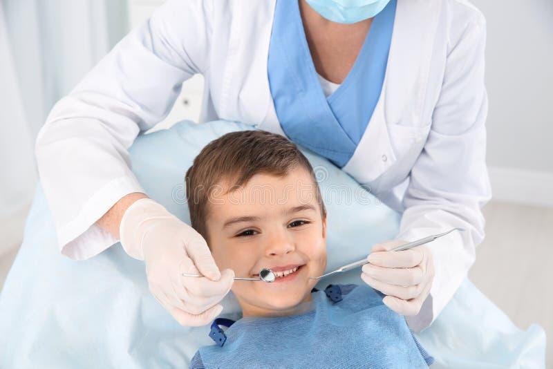 Dentista che esamina i denti del ragazzo sveglio in clinica fotografia stock libera da diritti