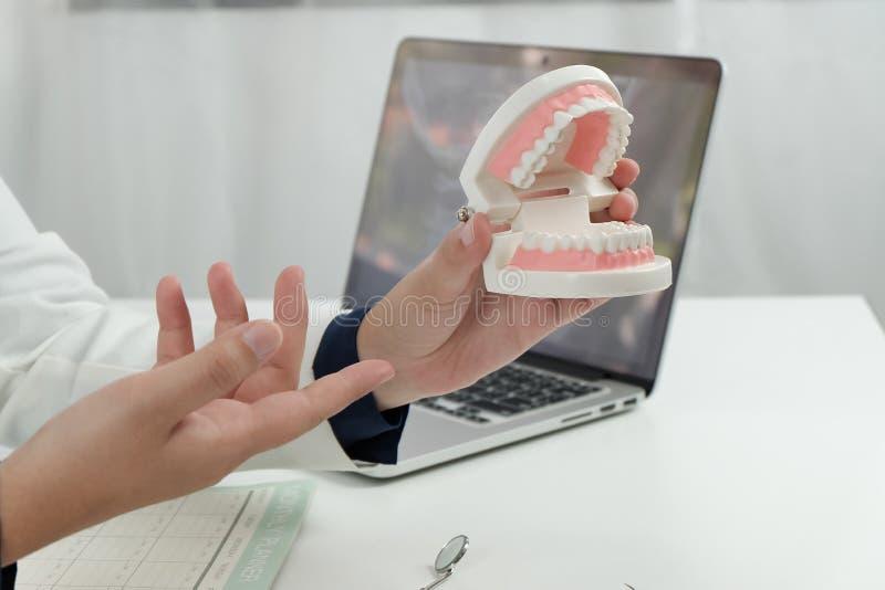 Dentista che esamina un trattamento medico paziente dei denti all'ufficio dentario fotografia stock