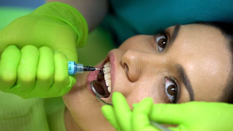 Dentista che mette gel blu sul dente, modellante pasta, odontoiatria cosmetica, primo piano fotografia stock