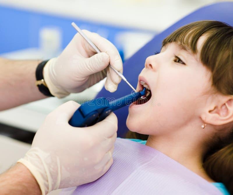 Dentista che per mezzo della pistola di riempimento dentaria sul bambino fotografie stock