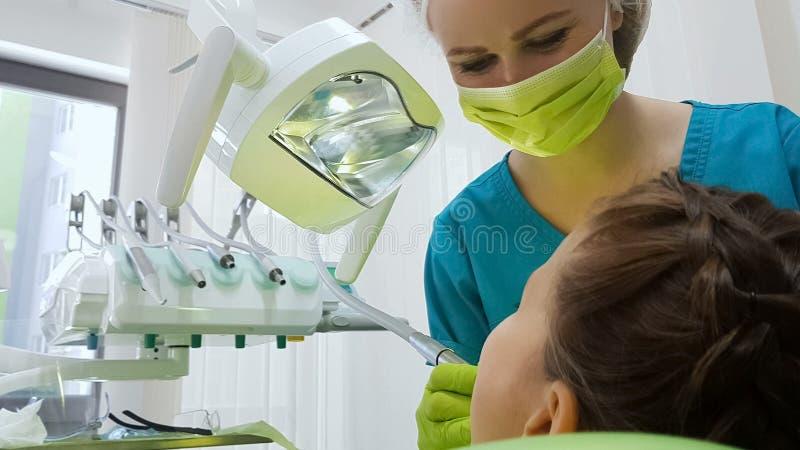Dentista che perfora con attenzione il dente dei bambini, clinica pediatrica moderna di stomatologia immagini stock libere da diritti