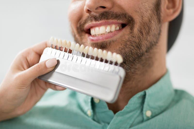 Dentista che sceglie colore del dente per il paziente alla clinica immagini stock libere da diritti