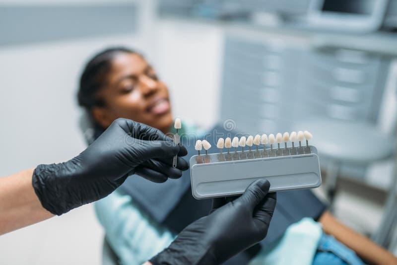 Dentista che sceglie la tonalità dei denti, clinica dentaria immagine stock libera da diritti