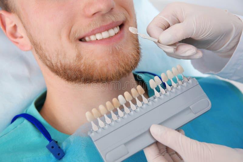 Dentista che seleziona colore dei denti del paziente con la tavolozza in clinica immagine stock libera da diritti