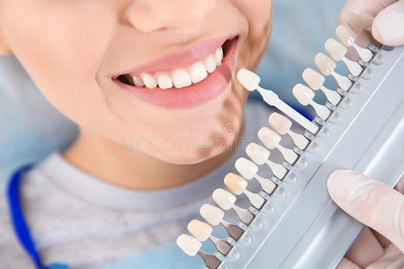 Dentista che seleziona colore dei denti del paziente con la tavolozza in clinica immagini stock