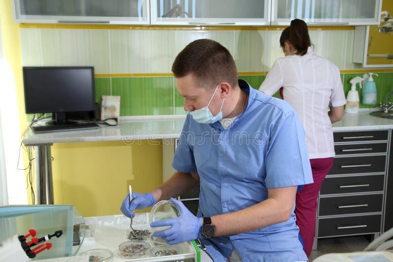 Dentista che tratta i denti del ` una s del paziente con gli strumenti dentari in clinica dentaria odontoiatria fotografia stock
